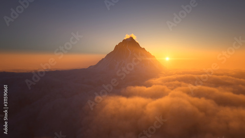 Mountain peak above the clouds at sunset - 311590661