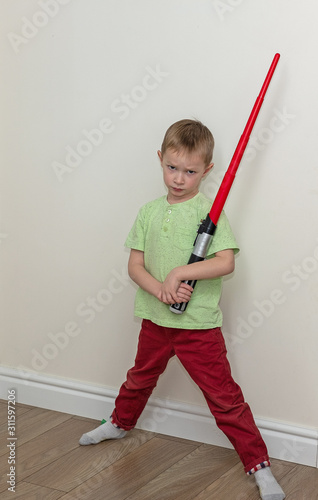 boy with an evil face holds a plastic lightsaber in the room Canvas Print