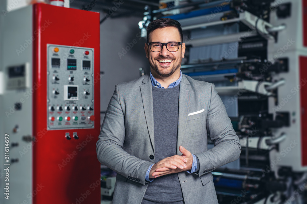 Fototapeta Industrial manager indoors in factory.Young businessman posing in factory.