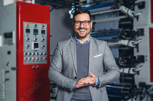 Fototapeta Industrial manager indoors in factory.Young businessman posing in factory. obraz
