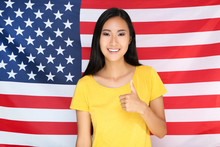 Young Woman Showing Thumb Up On American Flag Background