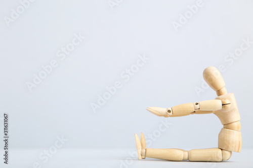 Wooden figure doing exercises on grey background Tablou Canvas