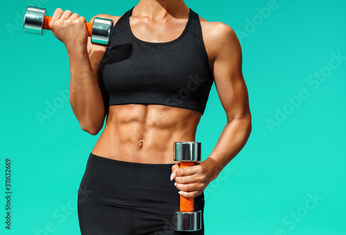 Cuadros en Lienzo  Close up of sporty young woman with muscular body on grey background with copy space
