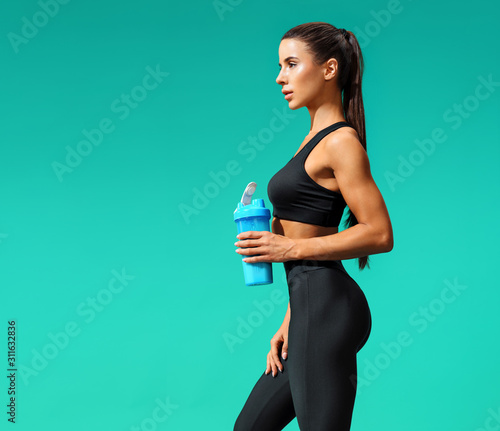 Fotografia Sporty girl holds shaker with protein cocktail