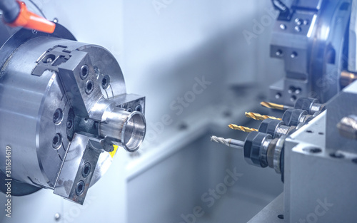Fototapeta CNC lathe machine drilling the metal rods with the drill tools obraz