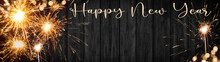 Happy New Year - Silvester Background Banner Panorama Long- Sparklers And Bokeh Lights On Rustic Wooden Texture, Top View With Space For Text