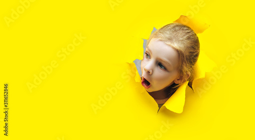 Funny red-haired child girl peeping through hole on yellow paper Fototapeta