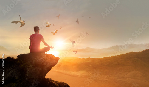 Foto Woman practices meditating and praying with free bird enjoying nature on the mountain sunset background, hope and faith concept
