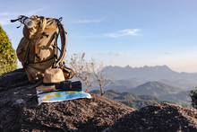 Binoculars And Map And Hat And Backpack On The Rock Mountains.