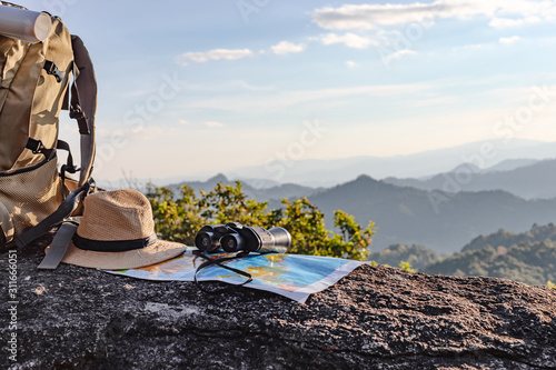 Photo binoculars and map and hat and backpack on the rock mountains.