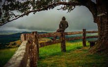 A Man Sitting On A Timber Fence Gazes Beyond The Hills  At The Upcoming Dark Clouds. Portrait Photography. Millaa Millaa Lookout, Atherton Tableland , Queensland, Australia.