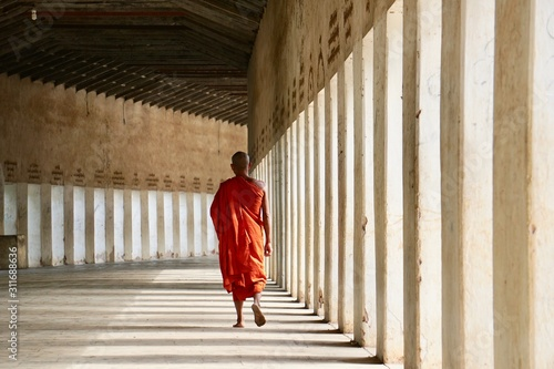 Photo Rear view of a buddhist monk walking along the corridor of the Shwezigon temple