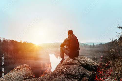 Fotomural Young man in jacket, pants and backpack sitting on rock looking to river Vltava and valley in sunset