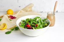 Bowl With Vegetable Salad And Jar Of Tasty Tahini On Table