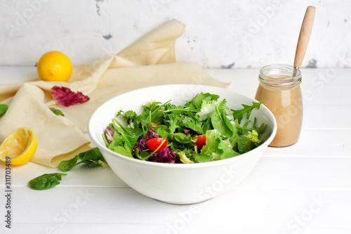Canvas Print Bowl with vegetable salad and jar of tasty tahini on table