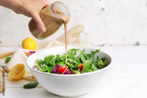 Photo Woman pouring tasty tahini from jar onto vegetable salad in bowl
