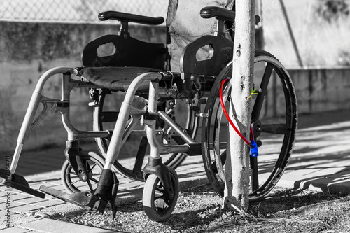 Photo Wheelchair attached to a tree with an anti-theft lock