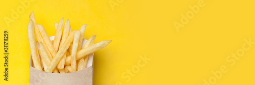 Web-banner with French fries in a cardboard box on the yellow background Canvas Print