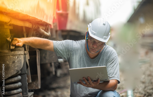 Canvastavla  Asian railroad engineer wearing helmet and inspecting checking train before serv