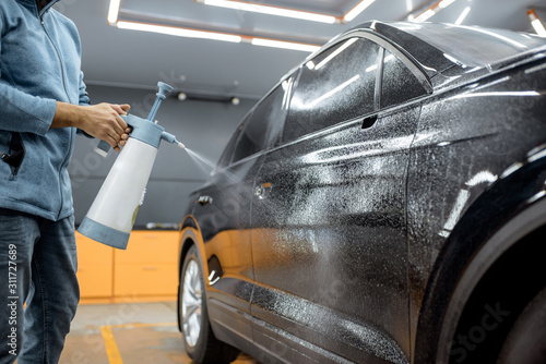 Fototapeta Car service worker splashing water on the car body, wetting it before anti-gravel film apply at the vehicle detailing service obraz