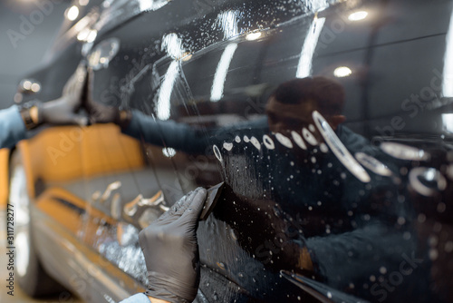 Worker sticking anti-gravel film on a car body with scrapper at the detailing vehicle workshop, close-up Tablou Canvas