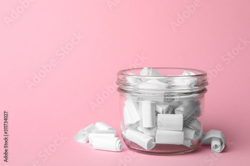 Carta da parati Glass jar full of rolled paper sheets on pink background, space for text