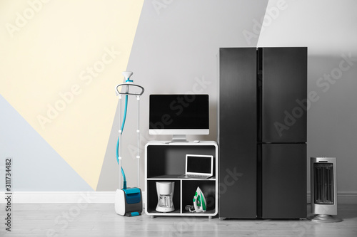 Canvastavla Modern refrigerator and other household appliances near color wall indoors