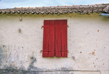Old Greek House With Dirty Weathered Wall And Painted Red Wooden Shutters On The Window.