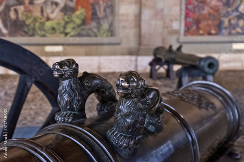 Fototapeta In Geneva, Switzerland, Under the arches of L 'Ancien Arsenal five cannons occupy the ground paved with pebbles. On its walls, one can admire three frescoes, signed Alexandre Cingria obraz