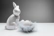 Porzelan Figur eines Osterhasen mit kleinen Körbchen Nestern mit Daunen Federn auf weiß schwarzen Hintergrund isoliert