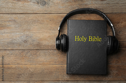 Cuadros en Lienzo Bible and headphones on wooden background, top view with space for text
