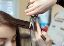 The Hairdresser Does A Haircut With Hot Scissors Of Hair To A Young Girl, A Brunette In A Beauty Salon.Professional Hair Care And Treatment.