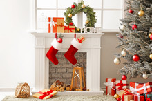 Christmas Socks With Gifts Hanging On Fireplace In Room