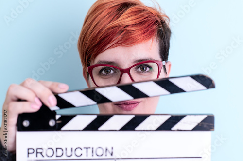 woman holding movie clapper against cyan background Fototapet