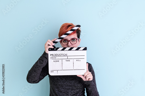 Fotografie, Tablou woman holding movie clapper against cyan background