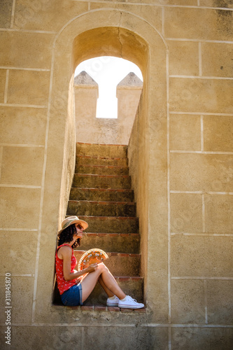 White woman taking a break from the hot on the old town of Badajoz in Spain
