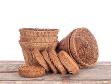 Coir, Coconut Fibre, Plant Pots And Growing Pellets, Discs Against White Background. Environmentally Friendly Peat Free Spring Gardening.