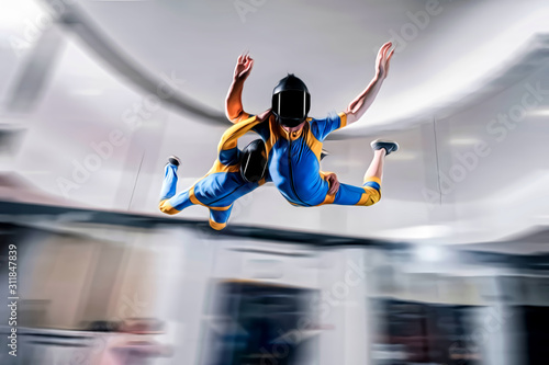 Fototapety, obrazy: Speed. Extreme people prefere sky sport. Fly men perfoms trick in air. Parachutist in blue and yellow suit is in free fall. Skydiving is sport without rules.