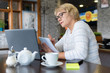A woman with a laptop looks at a document in a cafe, office