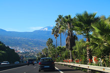 Highway TF-5 To Puerto Del La Cruz With View At The Snow Covered Volcano Teide And Palm Trees And Aloe At Roadside (Tenerife, Spain)