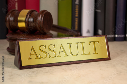 Photo Golden sign with engraved word assault with gavel on a desk