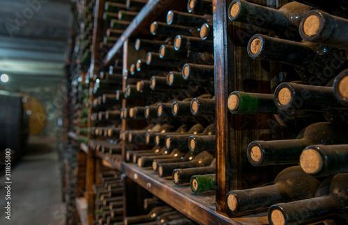 Photo dusty wine bottles on a wooden shelf in a wine cellar