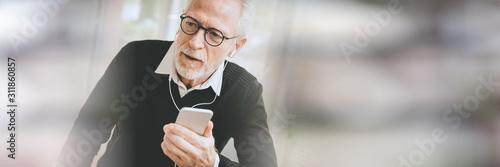 Businessman using earphones during conversation on mobile phone; panoramic banne Fototapeta