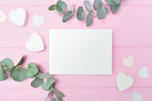 Valentines Day Or Wedding Mockup Scene With Blank Card, Eucalyptus Leaves Frame Paper Hearts Confetti And Wooden Pink Background, Empty Space For Your Text, Top View Flat Lay