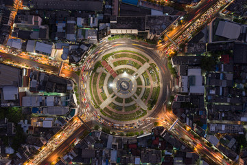Road roundabout with car lots Wongwian Yai in Bangkok,Thailand. street large beautiful downtown at night light. Aerial view , Top view ,cityscape ,Rush hour traffic jam