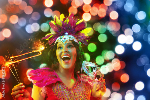 Obraz Beautiful young woman in carnival mask and stylish masquerade costume with feathers and sparklers in colorful bokeh on black background. Christmas, New Year, celebration. Festive time, dance, party. - fototapety do salonu