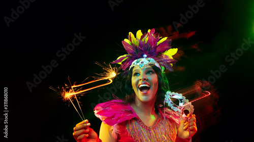 Fototapeta Beautiful young woman in carnival mask, stylish masquerade costume with feathers and sparklers inviting