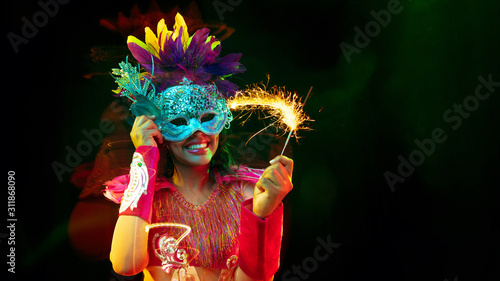 Obraz Beautiful young woman in carnival mask, stylish masquerade costume with feathers and sparklers inviting. Flyer for ad on black background. Christmas, New Year, celebration. Festive time, dance, party. - fototapety do salonu