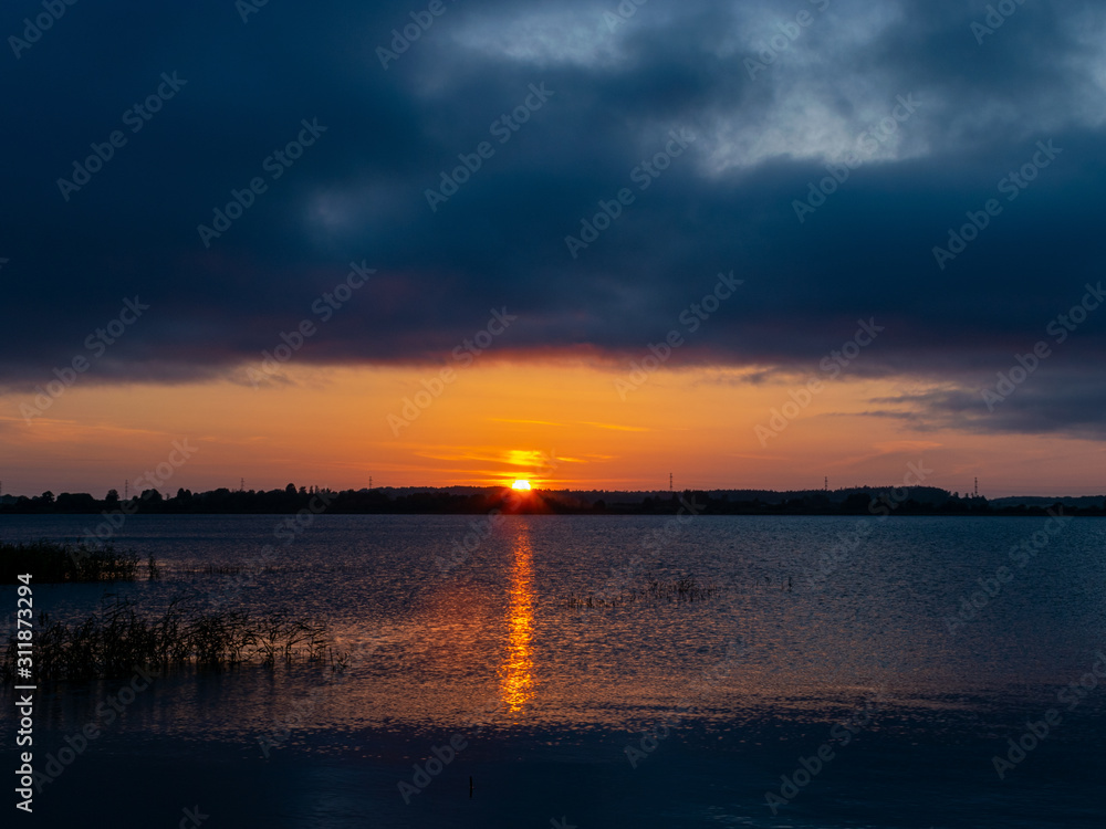 landscape with sunset in the background, lake sand and grass in the foreground