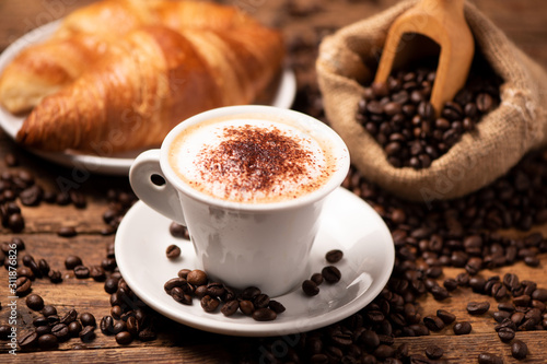 Fototapeta A cup of cappuccino with coffee bean as background. obraz